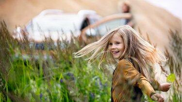 Glückliches Mädchen am Familienausflug mit dem Dacia Duster