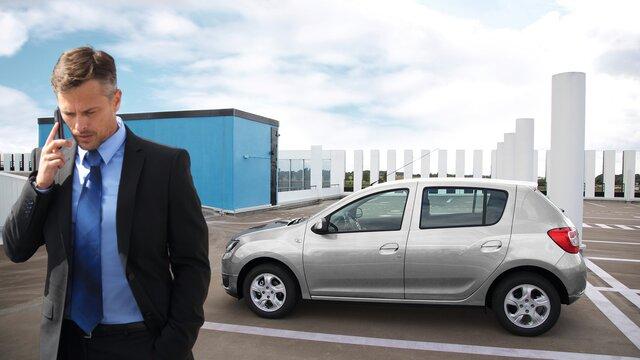 Geschäftsmann mit einem Dacia Sandero am Parkplatz