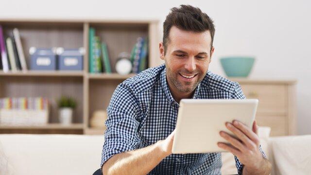 Glücklicher Mann beim Buchen eines Service Termin am Tablet