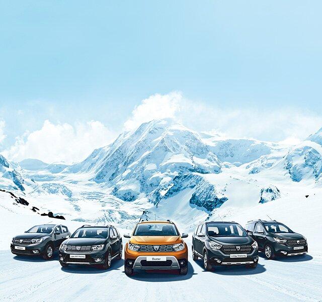 Alle Dacia Modelle in einer Reihe  im Schnee vor einem Berg