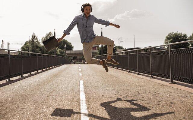 Mann bei einem Luftsprung weil er die Werkstattrechnung zurückgewonnen hat