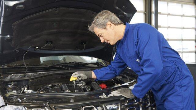 Mechaniker mit dem Motor eines Dacia Duster