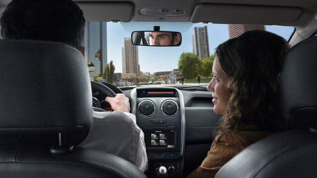Pärchen im Dacia unterwegs in der Stadt