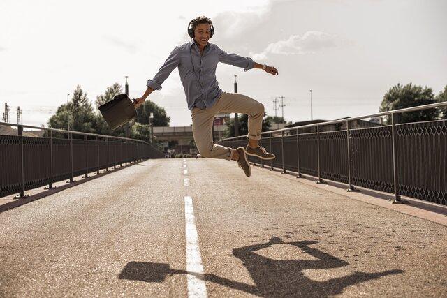 Mann mit Kopfhörern springt vor Freude weil er die Werkstattrechnung zurück gewonnen hat