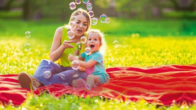 Mutter und Kind auf Decke beim Spiel