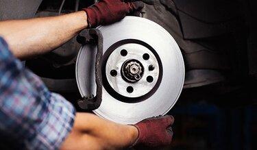 Werkstattmitarbeiter baut Bremsscheiben ein