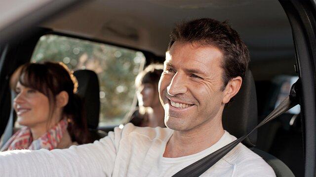 Lächelndes Paar mit Tochter in Renault Wagen