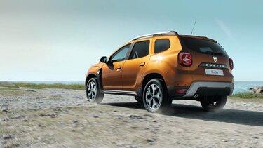 Dacia DUSTER Oranje rijdend in bergen