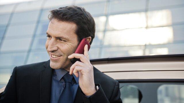 mężczyzna rozmawia przez telefon przed budynkiem