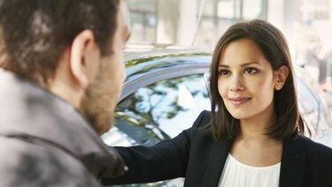 Ein Gespräch zwischen einen Mann und Frau vor ihrem Renault Neuwagen