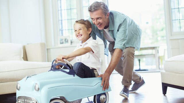 Vater und Sohn spielen mit einem Renault Spielzeugauto