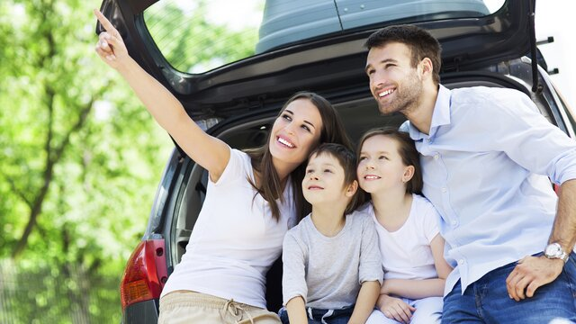4-köpfige Familie vor einem offenen Kofferraum