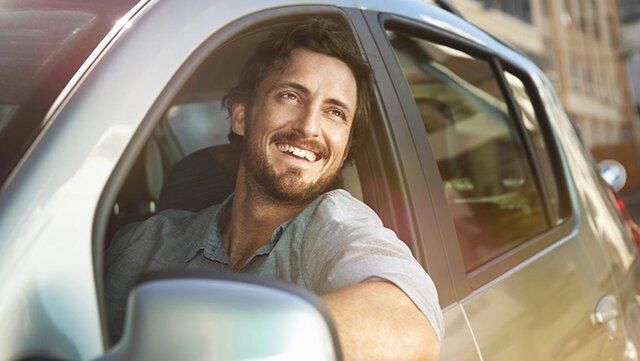 Glücklicher Mann in seinem Renault Neuwagen