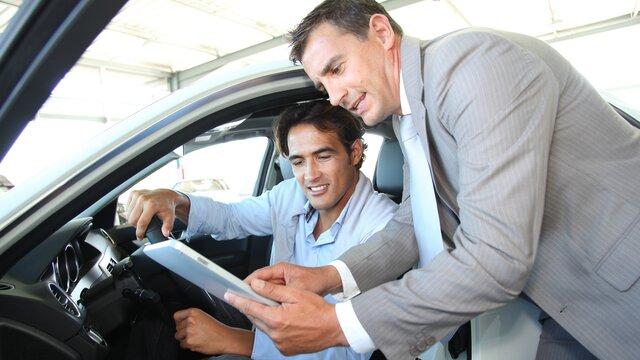 Renault Verkäufer zeigt einem Mann die Papier für den Renault