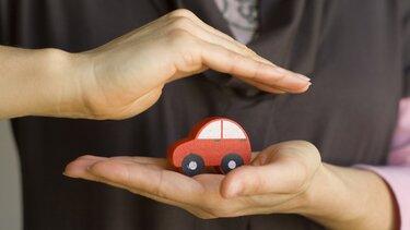 Ein rotes Holzauto in schützenden Händen