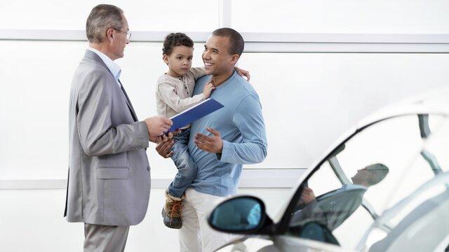 Ein Mann mit seinem Kind bekommen die Papiere für ihren neuen RENAULT überreicht