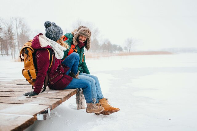Service Winter-Angebote - Two people sitting and smiling near of frozen lake