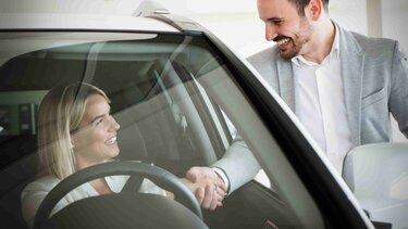 Mujer en un vehículo saludando a un hombre por la ventana