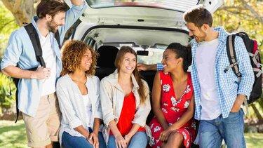 Grupo de amigos sonriendo en el baúl de un vehículo