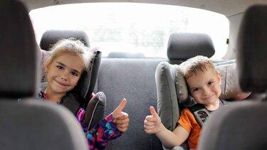 Niños sonriendo en el asiento de atrás de un vehículo