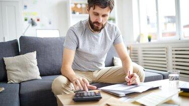 Hombre haciéndo cálculos en papel, con calculadora