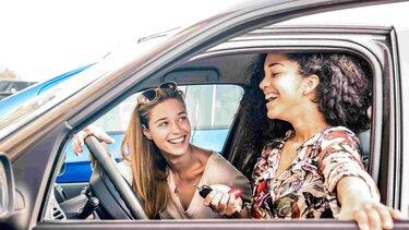 Mujeres sonríendo al interior de un vehículo