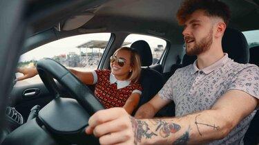 Pareja joven sonriendo al interior de un vehículo