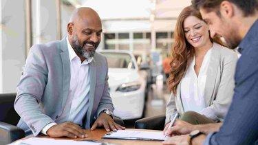 Una mujer y dos hombres revisando documentos mientras sonríen
