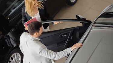 Hombre y mujer mirando el interior de un vehículo