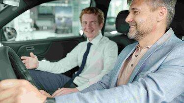 Dos hombres conversando al interior de un vehículo.