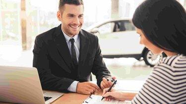 Mujer firmando un documento mientras un hombre le entrega las llaves del vehículo