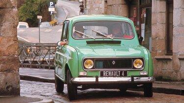 Grüner Renault R4 fährt mit zwei Insassen durch die Gassen