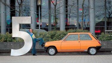orangener Renault 5 steht zusammen mit Frau auf der Straße
