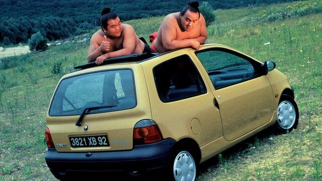 Zwei Sumoringer auf der Dachhaube eines alten Renault Twingo