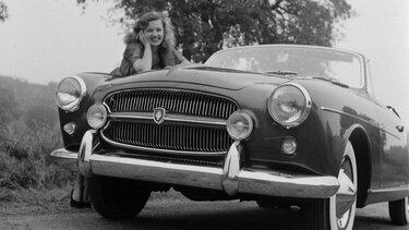 Frau lehnt sich 1950 auf Motorhaube vom Renault Fregate