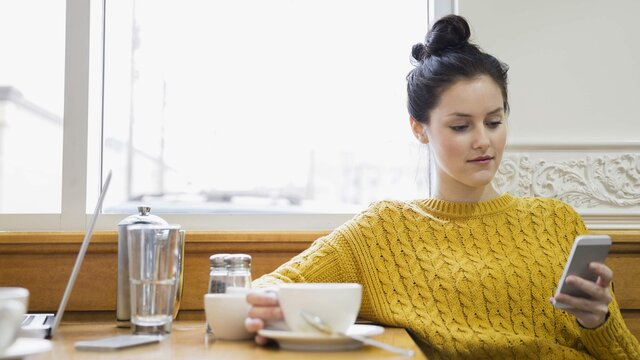 Frau mit Renault gelbem Pulli sitzt am Tisch und beschäftigt sich aufm Handy mit der MY Renault APP