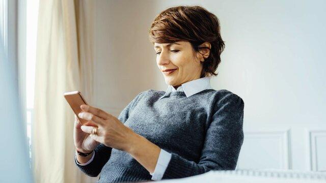 Braunhaarige Frau benutzt Renault Easy Connect auf Ihrem Handy