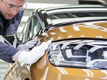 Mitarbeiter mit Handschuhen untersucht gelben Renault Wagen