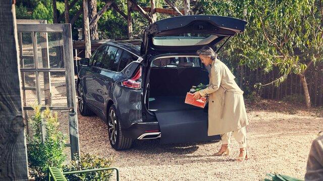Erwachsene Frau packt Kiste in den Kofferraum ihres Wagens