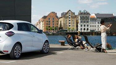 Weißer Renault ZOE parkt am Wasser und drei Menschen sitzen in Liegestühlen