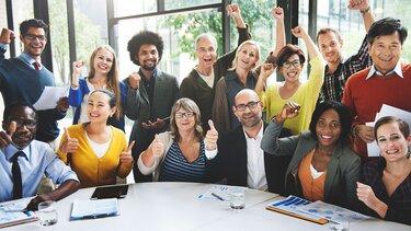 Vierzehn Mitarbeiter sind um einen Tisch versammelt und jubeln