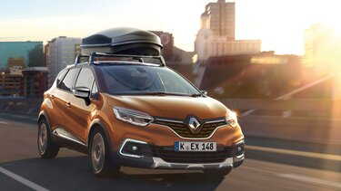 Orangener Renault Captur mit Dachbox fährt durch den Stadtverkehr