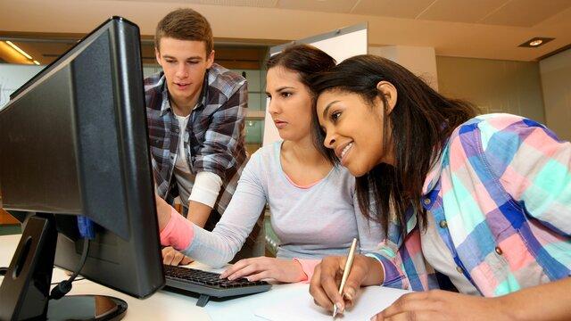 drei Jugendtliche schauen gemeinsam auf einen Rechner