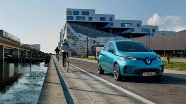 Blauer Renault ZOE fährt am Wasser entlang neben zwei Fahrrad-Fahrern