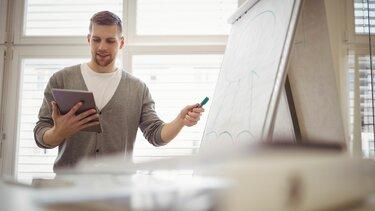 Junger Mann steht vor einem Flipchart mit Tablet und Marker in der Hand und erklärt etwas