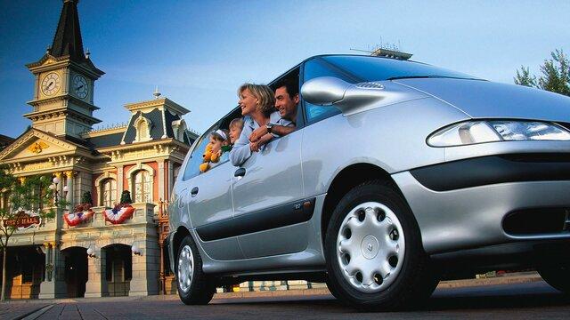 Familie mit zwei Kindern schaut aus den Fenstern eines grauen Renault Espace