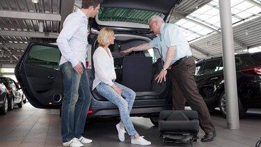 Autoverkäufer führt mit einem Paar einen Renault Wagen vor