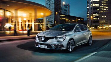 Grauer Renault Clio fährt durch die Stadt