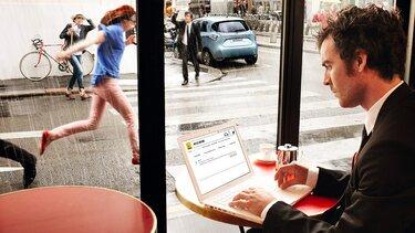 Mann arbeitet auf seinem Laptop in einem Cafe