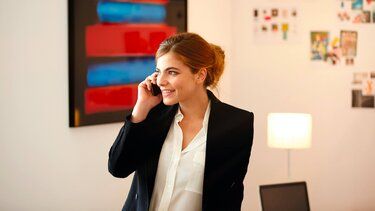 Frau mit schwarzer Anzugjacke telefoniert im Büro
